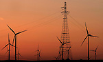 Windmills and high tension lines are silhouetted by the setting sun near Antioch, California.