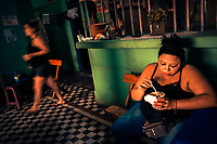 A Salvadoran sex worker eats lunch before beginning a work shift at a street sex bar in San Salvador, El Salvador, 7 April 2018. Although prostitution is not legal in El Salvador, dozens of street sex workers, wearing provocative miniskirts, hang out in the dirty streets close to the capital's historic center. Sex workers of all ages are seen on the streets but a significant part of them are single mothers abandoned by their male partners. Due to the absence of state social programs, they often seek solutions to their economic problems in sex work. The environment of street sex business is strongly competitive and dangerous, closely tied to the criminal networks (street gangs) that demand extortion payments. Therefore, sex workers employ any tool at their disposal to struggle hard, either with their fellow workers, with violent clients or with gang members who operate in the harsh world of street prostitution.
