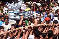 Procissão do  Círio de Nassa Senhora de Nazaré, que acontece a a mais de 200 anos na cidade de Belém e leva as ruas mais de um milhão e meio de romeiros.Promesseiros levantam a corda acompanhado por um pagador de promessas que agradece uma graça alcancada levando um barco na cabeça.<br />Belém Pará Brasil.<br />10/10/2004.<br />Foto Paulo Santos/Interfoto Cirio de Nazaré 2004