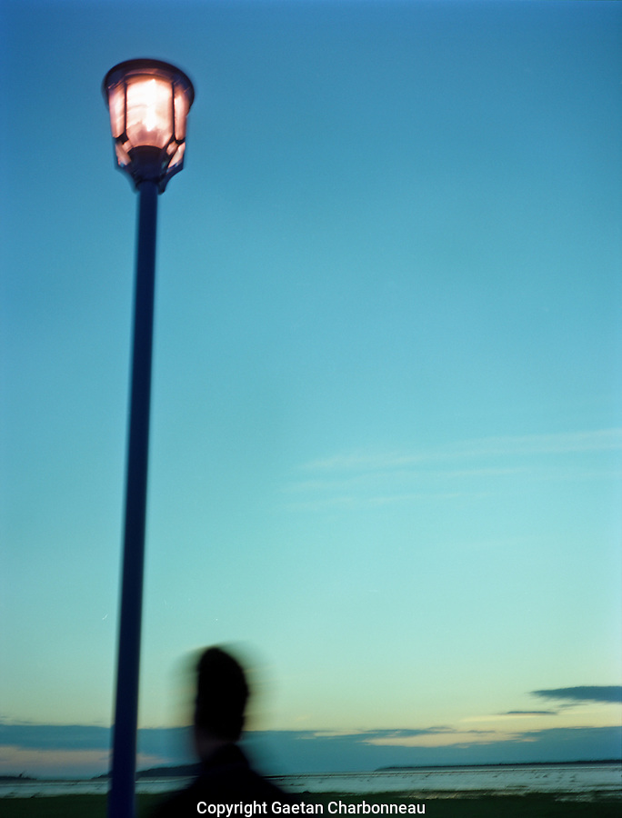 A silhouette walking by a lampost, at dusk, open sky in the backgroud