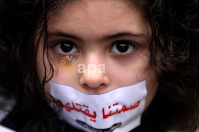 """A Palestinian girl covers her mouth with a sticker during a rally to show solidarity with Palestinian prisoners on hunger strike in Israeli jails, in Gaza City February 19, 2013. The sticker reads:""""Yes to hunger, no to kneeling."""". Photo by Ashraf Amra"""