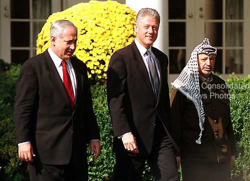 United States President Bill Clinton walks through the Rose Garden at the White House in Washington, D.C. on Thursday, October 15, 1998 with Israeli Prime Minister Binyamin Netanyahu, left, and Palestinian Authority Chairman Yasser Arafat, right, following their meeting in the Oval Office..Credit: Ron Sachs / CNP