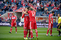 Chicago midfielders Marco Pappa (16, left), Sebastian Grazzini (10, middle), and Logan Pause (12) share a hug after Grazzini's penalty kick put Chicago ahead 1-0.  The Chicago Fire defeated the New England Revolution 3-2 at Toyota Park in Bridgeview, IL on Sept. 25, 2011.