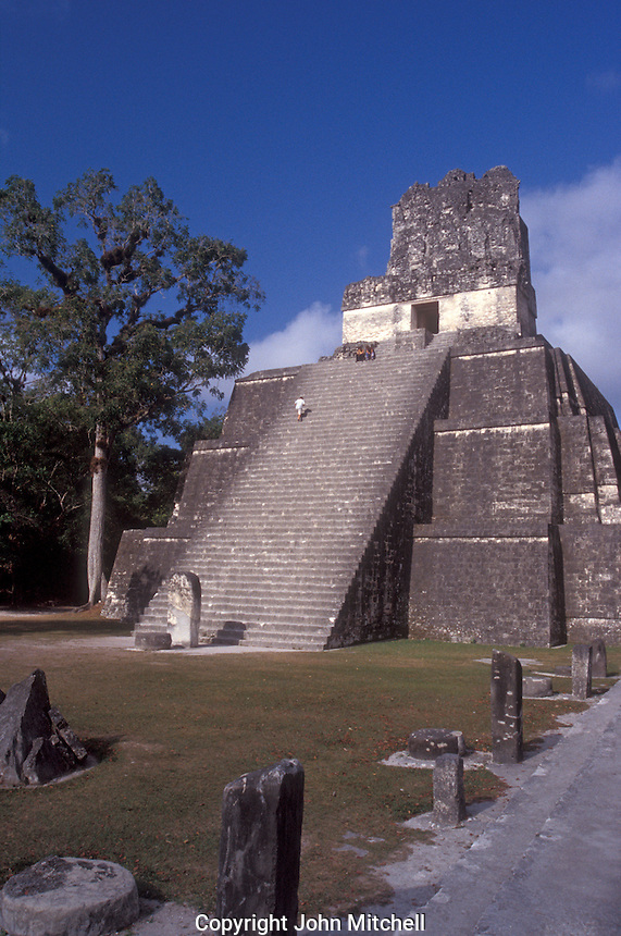 Tourist climbing Temple II or Temple of the Masks at the Mayan ruins of Tikal in Tikal National Park, El Peten, Guatemala