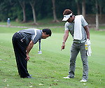 Thongchai Jaidee consults a rules official before he plays his second shot on the third fairway during Round 3 of the CIMB Asia Pacific Classic 2011.  Photo © Raf Sanchez / PSI for Carbon Worldwide