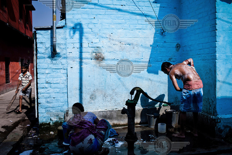 A young man from the Devanga community washes himself at a standpipe in the narrow lanes of Mahesh, Hooghly.