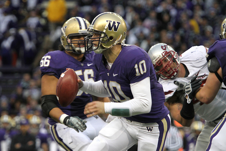Jake Locker (#10), University of Washington quarterback, scrambles out of the pocket during the Huskies Pac-10 conference football game against arch-rival Washington State at Husky Stadium in Seattle, Washington, on November 28, 2009.  Washington shut out the Cougars in their annual Apple Cup battle, 30-0.
