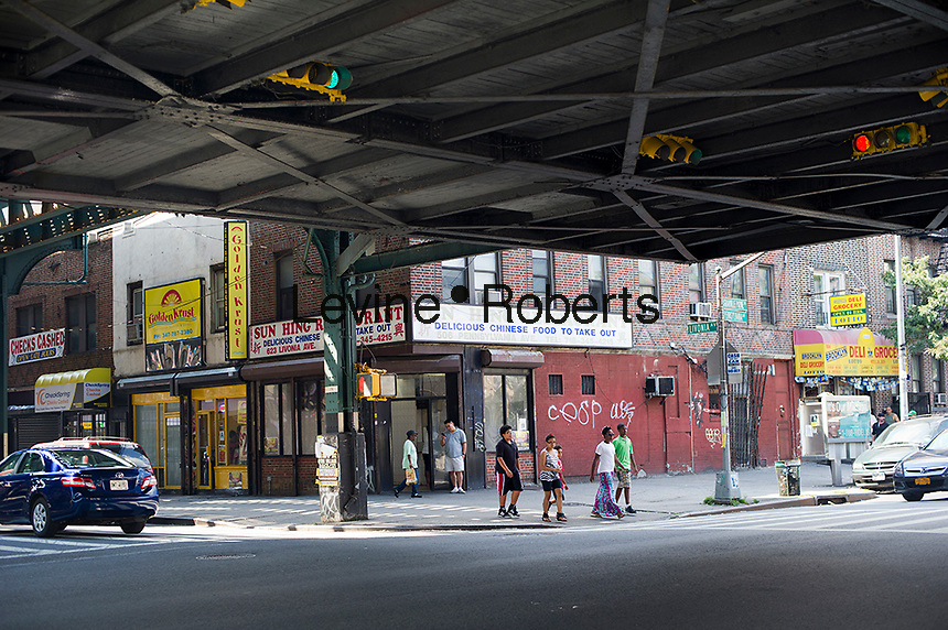 Pedestrians cross the street under the elevated subway tracks in the East New York neighborhood of Brooklyn in New York seen on Saturday, September 1, 2012. (© Frances M. Roberts)