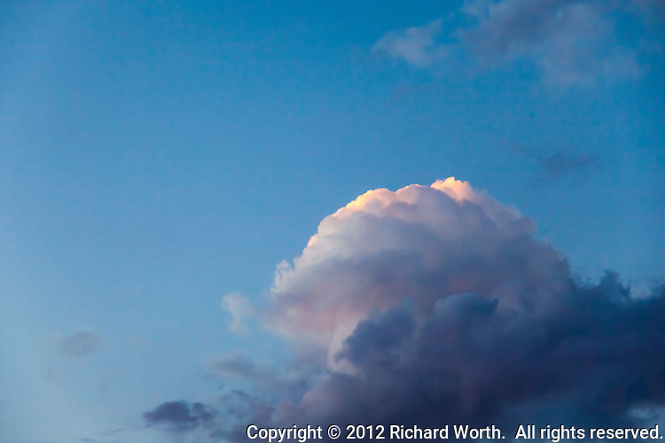 Golden sunset light illuminates the top most crest of a cloud against a blue sky.