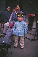 In Eighties China, clothing was almost uniformly drab and dull in colour and so the light blue jacket of this small boy in Suzhou makes him stand out from the crowd, a sensation with which he does not appear completely comfortable. On the other hand, his neo-military cap and buttoned-up look are more in keeping with those times.