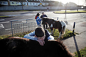 "Dublin, Ireland, January 6, 2011:.Young boys and their horses on Bell Camp housing estate..Since the beginning of crisis, between 10 and 20 thousand horses have become homeless or went in the hands of the youths in urban areas. Lots of Irish people who used to buy horses for fun during the boom years of ""Celtic Tiger"", now are abandoning them faced with expenditure of 35 Euro a week to properly maintain a horse. This animal previously worth 2000 Euro now can be purchased for as little as 80 Euro. New owners keep their horses in city greens, city ruins, or their house gardens, in very bad conditions. Most do not get much food, many are starving, dying, being mistreated..(Photo by Piotr Malecki / Napo Images)..Dublin, Irlandia, 6/01/2011:.Chlopcy i ich konie na osiedlu mieszkaniowym Bell Camp..Od poczatku kryzysu od 10 do 20 tysiecy koni zostalo wyrzuconych na ulice przez wlascicieli nie chcacych placic okolo 35 Euro/tydzien za ich utrzymanie. Wpadaja one czesto w rece mlodziezy z ubogich dzielnic miasta, ktora handluje nimi, bije, glodzi, trzyma w skrajnie trudnych warunkach, w przydomowych ogrodkach lub ruinach budynkow i szaleje na nich po miescie. Kon, ktory byl wart 2000 Euro teraz moze byc kupiony za 80. .Fot: Piotr Malecki / Napo Images."