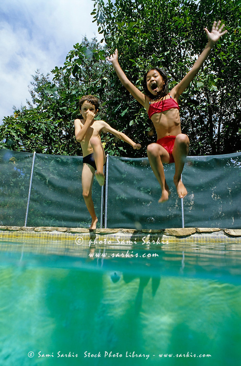 Young girl and boy leaping into a swimming pool, Provence, France.