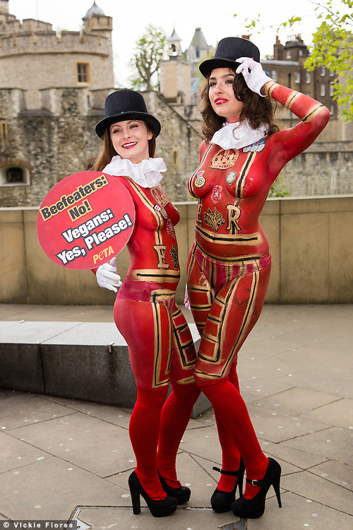 """Two female PETA demonstrators with their bodies painted to look like """"Beefeaters"""" (Yeoman Warder) stand outside the Tower of London asking people to give up eating meat. The campaign has been timed to fall one day before St George's Day."""