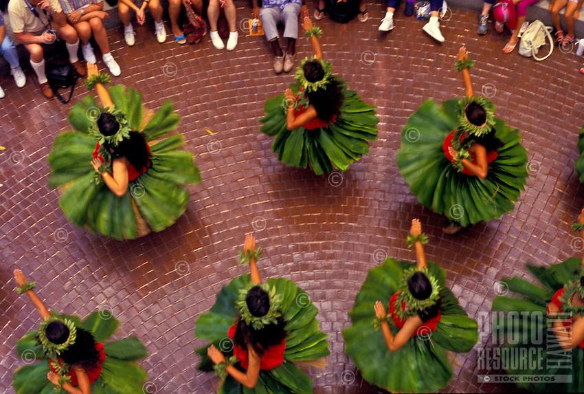 Spectators watch Molokai hula dancers twirl their ti-leaf skirts during a performance at Ward Warehouse in Honolulu.