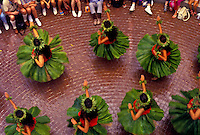 Spectators watch Molokai hula dancers twirl their ti-leaf skirts during a performance at Ward Warehouse in Honolulu.
