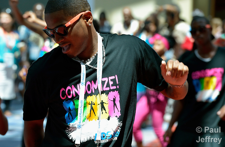 A youth dances as part of a promotion for condoms during the XIX International AIDS Conference, which brought more than 23,000 people to Washington, DC, in July 2012.