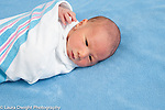 3 day old newborn baby boy closeup portrait swaddled in receiving blanket