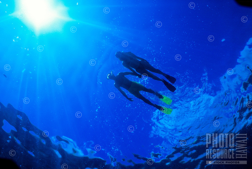A young couple visiting Oahu enjoys snorkeling over the coral reefs of Hanauma Bay looking for colorful sea creatures.