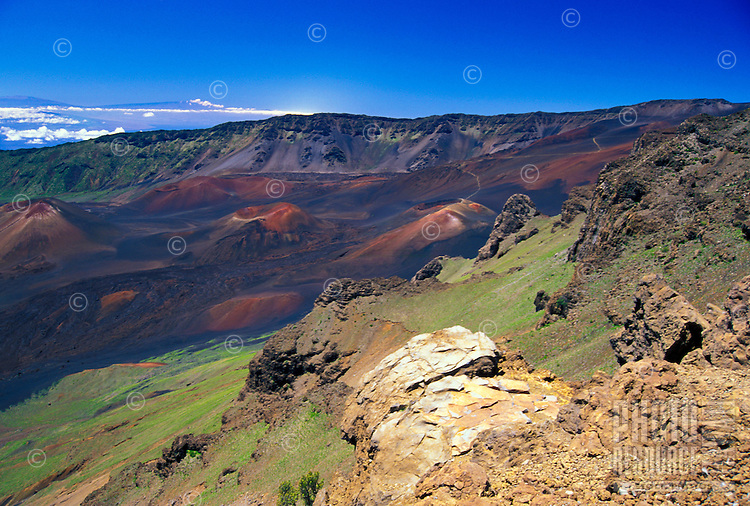 "The Haleakala National Park and ""crater"" with the summits of the Big Island's Mauna Kea and Mauna Loa 80 miles in the distance. Cinder cones denoting old lava flows and eruptions are below."