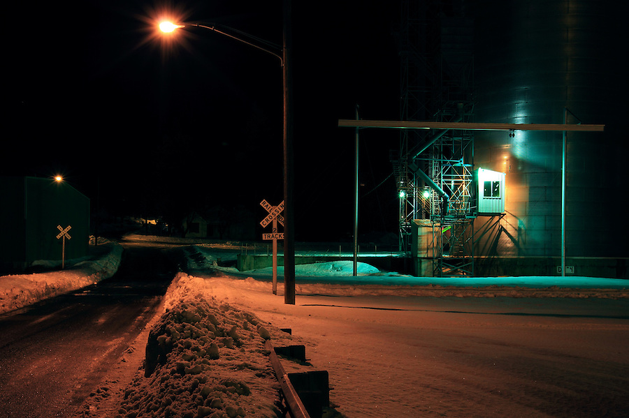 A railroad crossing and grain silo seen in the evening during winter in Fairfield, Washington.