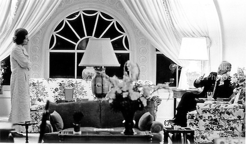 United States President Gerald R. Ford makes a late night phone call involving the evacuation of Saigon, South Vietnam from the Residence at the White House in Washington, D.C. on April 28, 1975.  First lady Betty Ford looks on from left.<br /> Mandatory Credit: David Hume Kennerly / White House via CNP