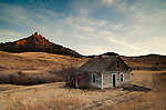 An abandoned homestead in Cascade County, Montana is seen near sunset with a warmly-lit mountain in the background.