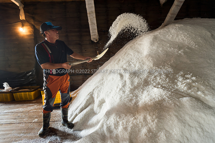 9/8/13 -- Jeungdo Island, Jeonnam Province (Jeollanam-do), South Korea<br /> <br /> Workers at the Taepyeong Salt Farm. Jeungdo began to produce salt around 1950. Jeungdo's sea salt has a high mineral content and exceptional taste. It is harvested by hand in the traditional way, which is the same method used by the upscale French sea salt brand, Guerande. Seawater is dried in shallow pools using only the sun and the wind. Jeungdo&rsquo;s Sea salt can be purchased both in bulk and in small individual packages. Unlike processed table salt, it is rich in minerals and beneficial for your health. HERE: Ghun Joong Hwan.<br /> Photograph by Stuart Isett<br /> &copy;2013 Stuart Isett. All rights reserved.