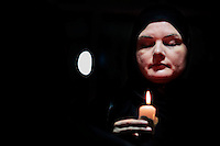 A Pakistani woman prays in a candlelight vigil to pay tribute to victims of Tuesday's Taliban attack on a military-run school in Peshawar, inside the Pakistani Embassy complex in Dhaka, Bangladesh.