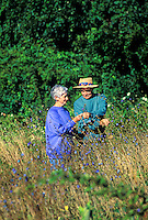 Senior couple out for a walk and picking wildflowers.