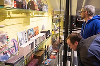 "Ed Tumavicus (blue hoodie, glasses), of Portland, Maine, and Peter Amann, of Scarborough, Maine, look at vintage radios and music memorabilia on display in a hallway off the lobby of The Verb Hotel in the Fenway neighborhood of Boston, Massachusetts, USA, on Friday, Dec. 4, 2015. The hotel is considered a ""boutique hotel"" and has collections on display throughout the premises of music memorabilia from the Boston area. Tumavicus and Amann were staying in the hotel for the weekend while they attended a conference in Boston. The pair reminisced about old Boston-area DJs and the radios they used to have while looking at the hotel's collection."