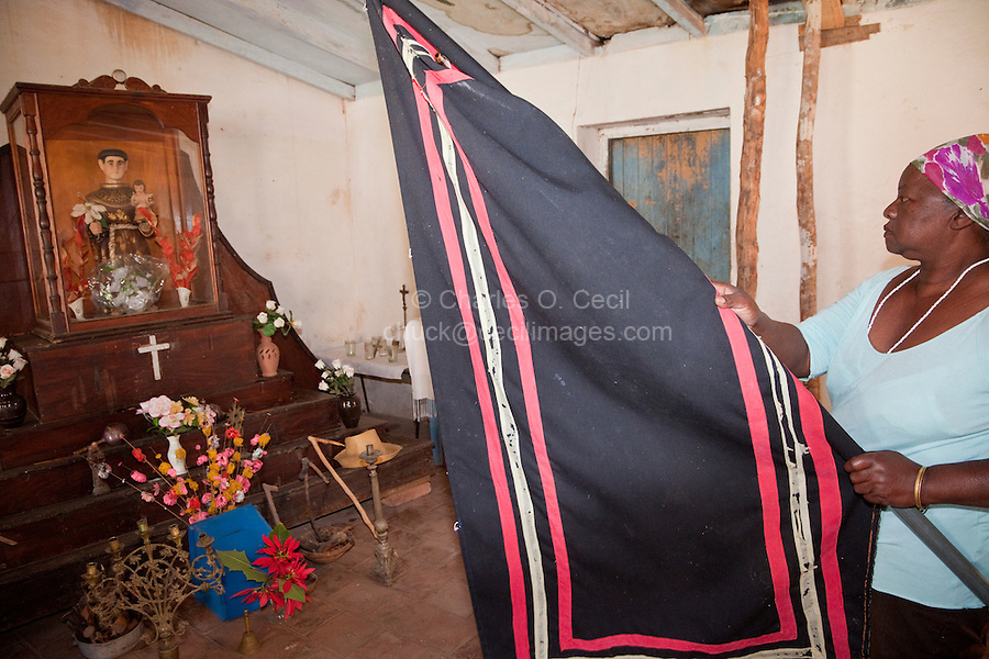 Cuba, Trinidad.  Woman Raising Flag in front of Shrine to Saint Anthony (San Antonio), representing the African god Ogun,  while Performing an Afro-Cuban Religious Ceremony.