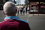 West Ham United 2 Crystal Palace 2, 02/04/2016. Boleyn Ground, Premier League. A home fan crossing Green Street near the Boleyn Ground before West Ham United hosted Crystal Palace in a Barclays Premier League match. The Boleyn Ground at Upton Park was the club's home ground from 1904 until the end of the 2015-16 season when they moved into the Olympic Stadium, built for the 2012 London games, at nearby Stratford. The match ended in a 2-2 draw, watched by a near-capacity crowd of 34,857. Photo by Colin McPherson.