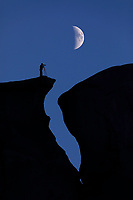 Silhouetted crack in mesa and moon, near Monument Valley, Arizona