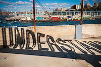"Projected shadow of the rotating ""Understanding"" public art sculpture in Brooklyn Bridge Park in New York on Sunday, October 23, 2016. ""Understanding"" by the artist Martin Creed features a 25 foot tall rotating red sculpture spelling out the word understanding reminiscent of a billboard on the side of a highway.  (© Richard B. Levine)"