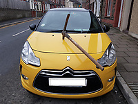 Pictured: The yellow Citroen car with a pickaxe embedded in its bonnet in in Llanbradach, near Caerphilly, Wales, UK.<br /> Re: A car owner found a pickaxe had been lodged in the centre of its bonnet.<br /> The damage happened on 5th of February when the yellow Citroen DS3 was parked on a street in Llanbradach, near Caerphilly, Gwent Police said.<br /> Officers have posted a picture of the car on Twitter to appeal for witnesses to come forward.<br /> It said it regarded it as an act of criminal damage and asked that anyone with information contact the force.