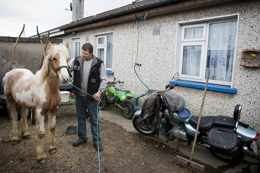 John Franklin is pictured with his horse Cindy that he keeps in his stables in his back yard of his bungalow with his pigeons, hens and collection of motorbikes in Delmage Park, Moyross, Limerick, Ireland