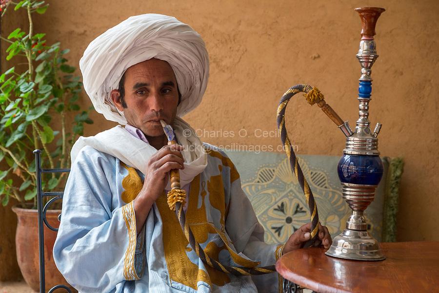 Near Ait Oudinar, Dades Gorge, Morocco.  Young Berber Man Smoking a Hookah (Shisha).
