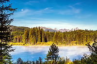Full moon over the Mission Mountains and Summit lake on a cool summer morning.