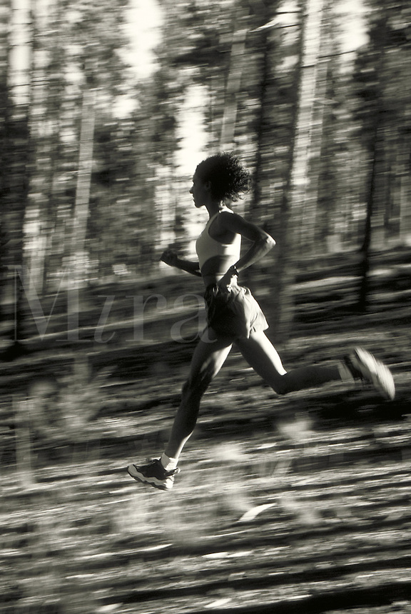 African-American woman running in Colorado forest. Melissa Terhorst MR 615. Colorado.