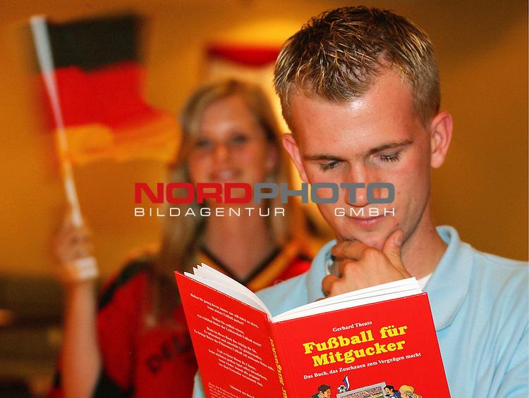 WM Fuflball Fussball Weltmeisterschaft 2006, Fanartikel, Stefan Lattemann (20 Jahre) ist begeisteter Eishockeyfan, um Fuflball zu verstehen hat er sich ein Buch zum Thema zugelegt und w&permil;hrend seine Freundin Pia Mildner Deutschlands Siege feiert studiert er fleiflig die Spielregeln, B&cedil;cher gibt es ab 3,99 Euro &cedil;berall wo es B&cedil;cher gibt, und viele werden zur Zeit reduziert, Foto &copy; nordphoto *** Local Caption *** Foto ist honorarpflichtig! zzgl. gesetzl. MwSt.<br /> Belegexemplar erforderlich<br /> Adresse: nordphoto<br /> Georg-Reinke-Strasse 1<br /> 49377 Vechta