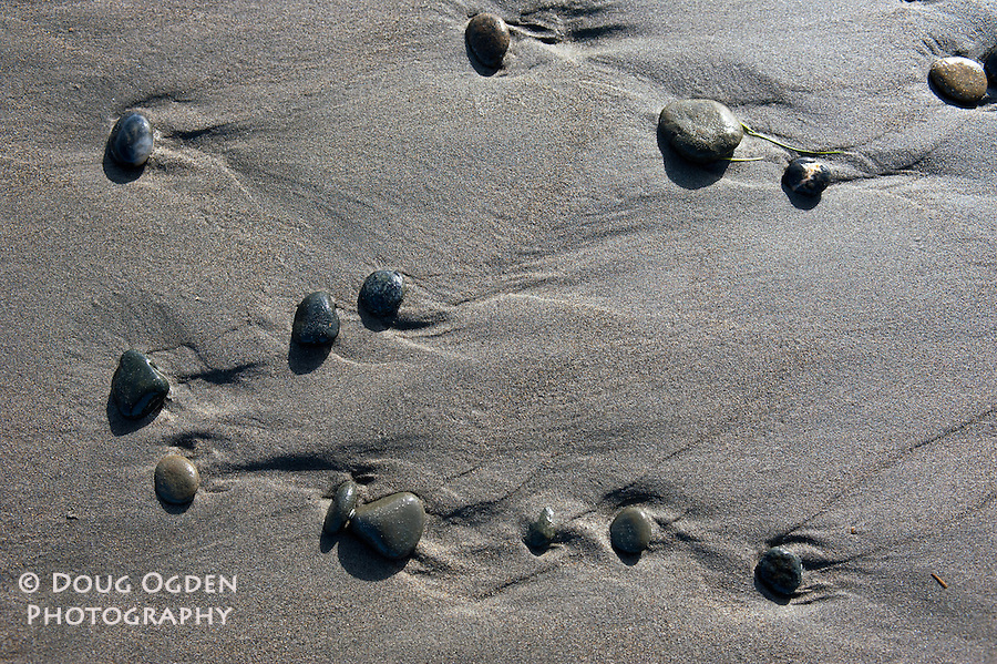 Stones on a beach appearing to be in formation with their vortices showing