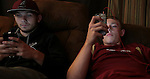 Kevin Whitaker (right) and teammate Stefan Lewis, 18, stare at their phone screens at Whitaker's house in Hyden, Ky. on Friday, October 11, 2013. Photo by Adam Pennavaria