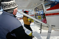 Volunteer pilot Diana Moroney loads her Cessna 185 at the Willow airport during the first day of flying straw, musher's dog food bags and people food & gear out to checkpoints south of the Alaska Range.  Saturday Feb. 21, 2009  Iditarod 2009