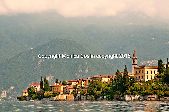 Varenna, a town on Lake Como, Italy as seen from the water on the South side of the town with the mountains and fog in the background