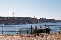 Three young people sitting on a bench on Riddarholmen looking out over Riddarfjarden and Soder. Stockholm. Sweden, Europe.