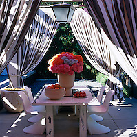 The privacy and shade of this outdoor dining area situated on one side of the pool is ensured with the use of generous striped curtains