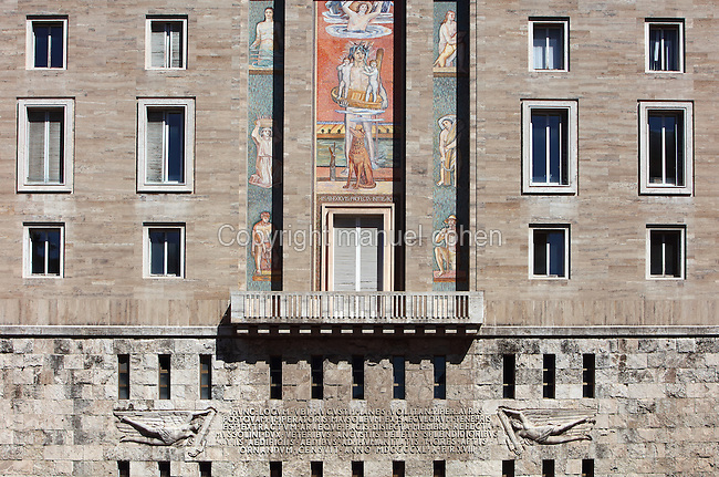 Reliefs, inscription and mural on the apartment buildings on the Piazza Augusto Emperatore, Rome, Italy, built in Fascist style with antique inspiration. Fascist architecture developed in the late 1920s and 1930s, as a modernist style in times of nationalism and totalitarianism under Benito Mussolini. It is characterised by large, square, symmetrical buildings with little or no decoration, often inspired by ancient Rome and designed to convey strength and power. Picture by Manuel Cohen