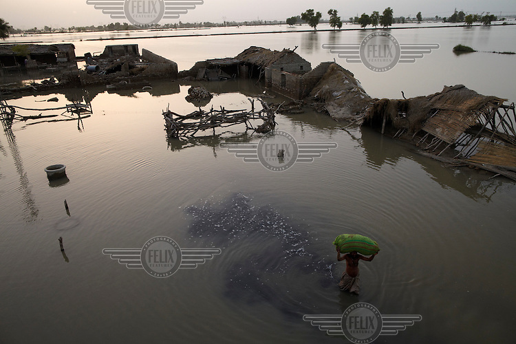 A man removes cattle feed from flooded buildings near Karampur, Sindh province, Pakistan.