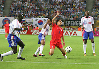Jung Hwan Ahn (9) of the Korea Republic is brought down by Vikash Dhorasoo (8) of France .The Korea Republic and France played to a 1-1 tie in their FIFA World Cup Group G match at the Zentralstadion, Leipzig, Germany, June 18, 2006.