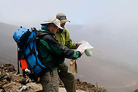 Two male hikers checking a trail map in the cloud engulfed crater in HALEAKALA NATIONAL PARK on Maui in Hawaii USA
